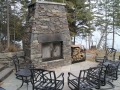 Outdoor fireplace featuring custom forged doors and wood rack
